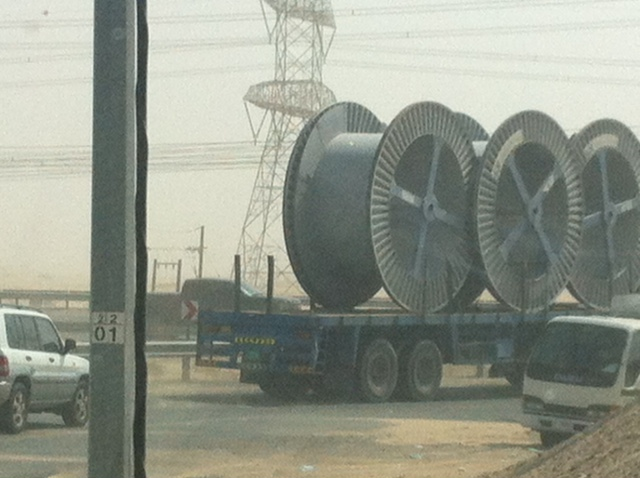 So I'm running late. I'm on the road that leads from our compound to the exit – a road on which there are speed bumps – steep ones, that practically stop your car in its tracks. And I find myself stuck behind a slow-moving construction vehicle, transporting … giant cotton reels?