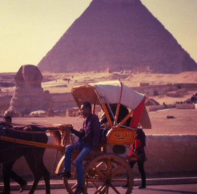 Sphinx: A man rides his horse and carriage past a scene that's been part of the landscape for thousands of years